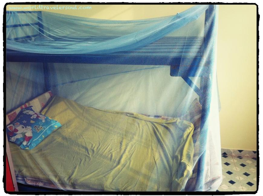 Instalando la mosquitera en mi cama del orfanato.